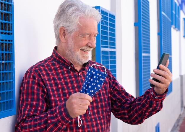 Glücklicher älterer mann nimmt während eines videoanrufs mit seinem smartphone die schützende gesichtsmaske ab. weißer und blauer hintergrund