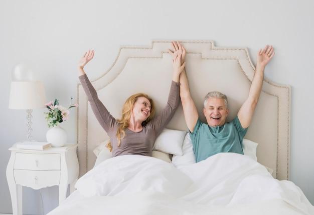 Glücklicher älterer mann und frau mit den händen oben