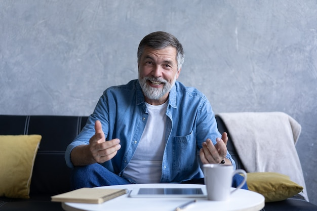 Glücklicher älterer rentner-blogger, der kamera-aufnahme-vlog betrachtet, lächelnder alter älterer großvater, der mit der webcam spricht, online-fernanruf oder video-chat auf dem sofa zu hause sitzen