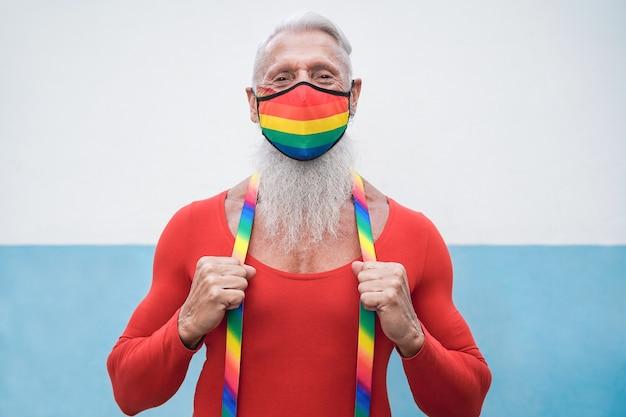 Glücklicher älterer schwuler mann, der regenbogenfahnenmaske bei lgbt parade trägt