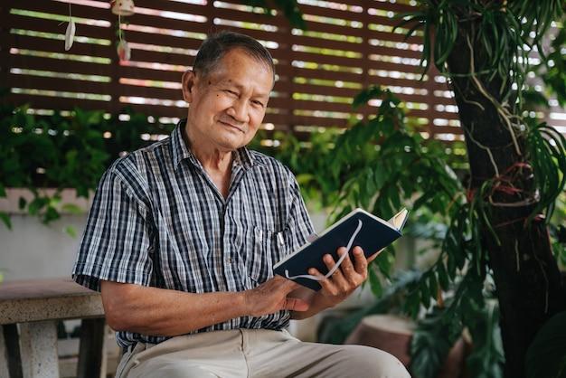 Glücklicher älterer thailändischer mann, der auf marmorstuhl unter dem baum sitzt und buch liest, gesundes seniorenkonzept