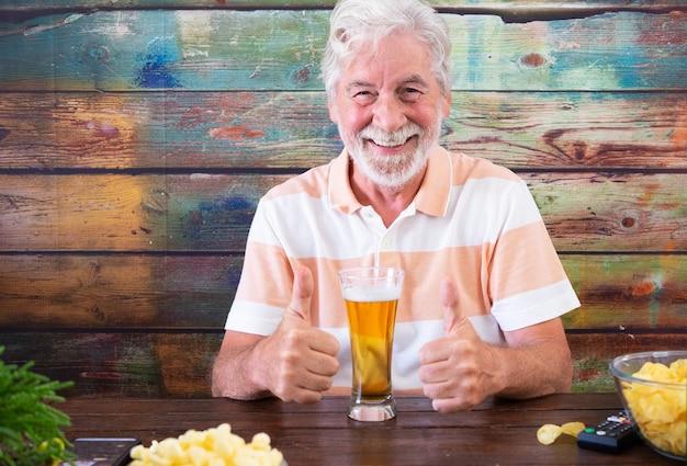 Glücklicher älterer weißhaariger mann, der mit bier und pommes am holztisch sitzt, macht positives zeichen