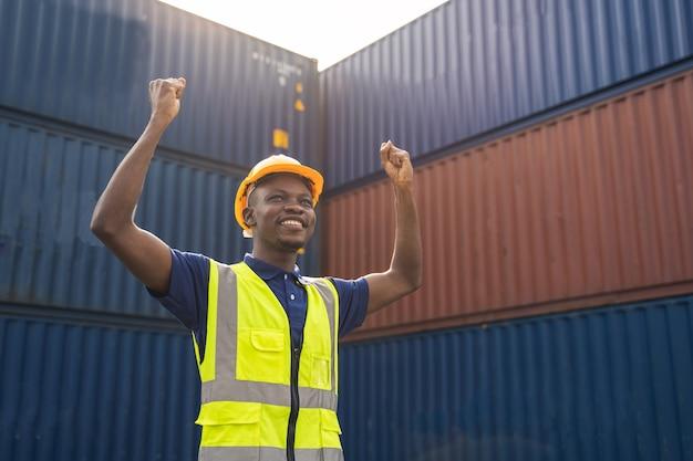 Glücklicher afrikanischer arbeiter, der smailt, am containerarbeitsplatz steht und hand mit glück und erfolg zeigt