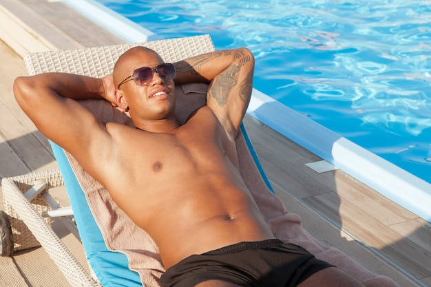Glücklicher afrikanischer athletischer mann, der nahe dem schwimmbad am luxusresort entspannt. attraktiver muskulöser mann, der am pool ruht, raum kopieren