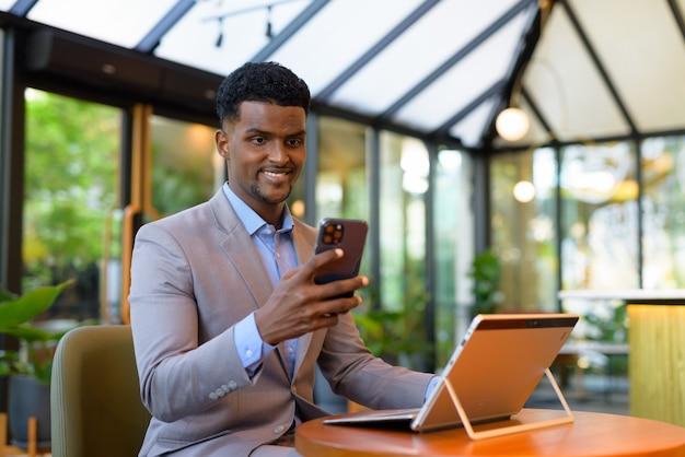 Glücklicher afrikanischer geschäftsmann, der ein virtuelles webinar-treffen im café mit laptop und mobiltelefon hat