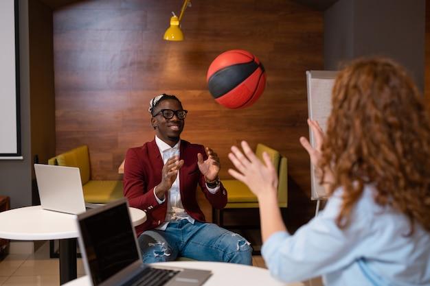Glücklicher afrikanischer kerl im klugen lässigen wurfball zu seinem gruppenmitglied, während beide nach dem unterricht im college-café sitzen
