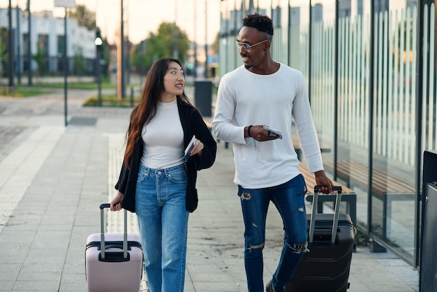Glücklicher afrikanischer kerl mit seiner lächelnden asiatischen frau, die pässe mit tickets hält und koffer nahe flughafen trägt.