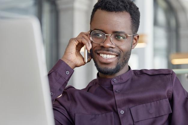 Glücklicher afrikanischer männlicher geschäftsarbeiter mittleren alters hat ein angenehmes gespräch mit einem freund über ein smartphone und teilt den erfolg bei hohen umsätzen