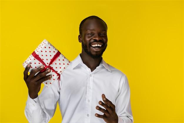 Glücklicher afrikanischer mann, der an der kamera lächelt und ein geschenk hält
