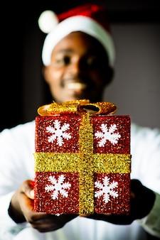 Glücklicher afrikanischer mann, der ein weihnachtsgeschenk gibt.