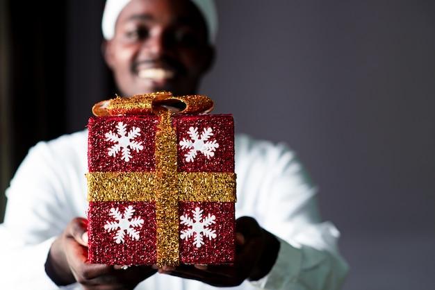 Glücklicher afrikanischer mann, der eine weihnachtsgeschenkbox gibt.