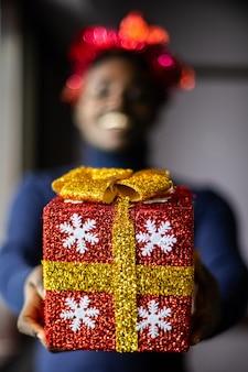 Glücklicher afrikanischer mann, der eine weihnachtsgeschenkbox gibt