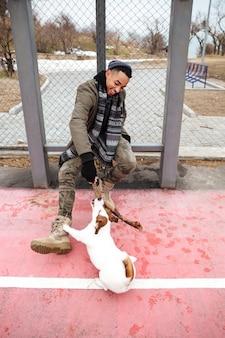 Glücklicher afrikanischer mann, der lächelt und mit hund draußen spielt