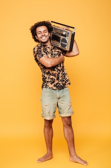 Glücklicher afrikanischer mann, der mit tonbandgerät steht