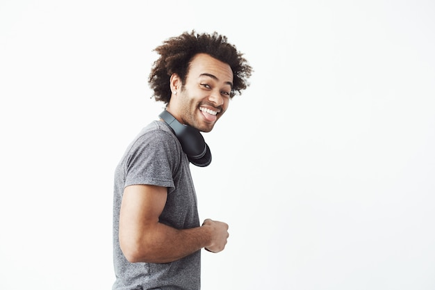Glücklicher afrikanischer mann, der st kamera sieht, die zunge zeigt