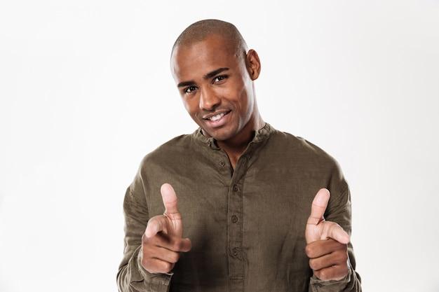 Glücklicher afrikanischer mann, der zeigt und schaut