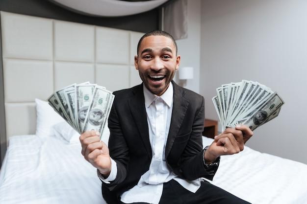 Glücklicher afrikanischer mann im anzug mit geld in den händen, die auf bett mit offenem mund im hotelzimmer sitzen
