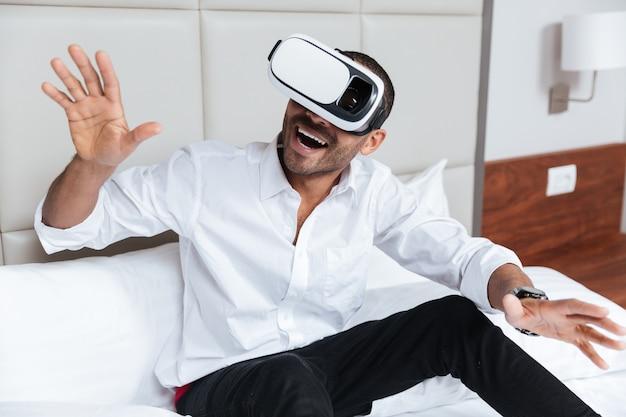 Glücklicher afrikanischer mann im hemd mit offenem mund unter verwendung des virtual-reality-geräts, das auf dem bett im hotel sitzt