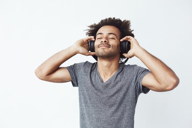 Glücklicher afrikanischer mann lächelnd, der musik in den kopfhörern hört.