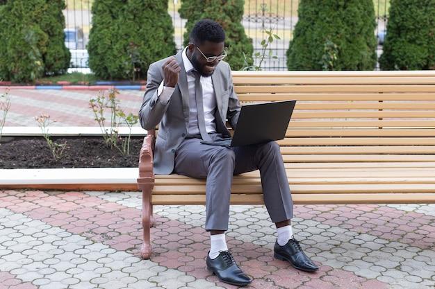 Glücklicher afroamerikaner auf der straße mit laptop, freiberuflich