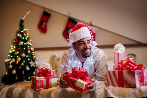 Glücklicher afroamerikaner mit weihnachtsmütze und geschenken herum.