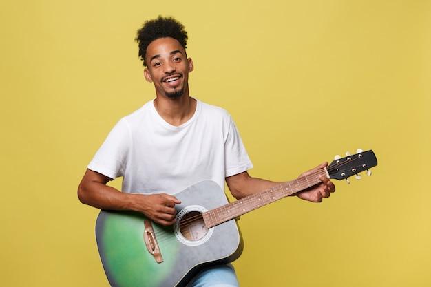 Glücklicher afroamerikaner-musikermann, der mit einer gitarre, über goldenem gelbem hintergrund aufwirft.