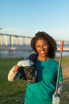 Glücklicher afroamerikanerfreiwilliger, der im stadtpark aufwirft