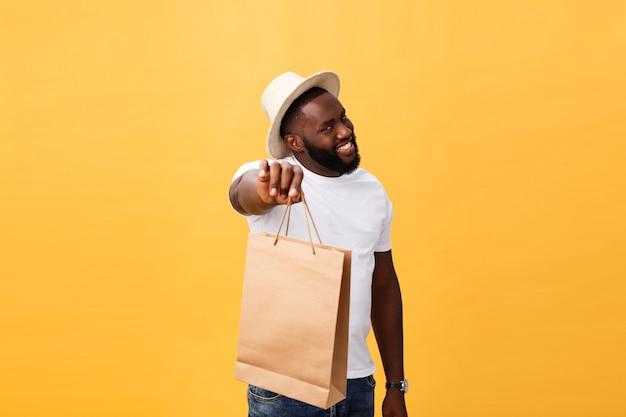 Glücklicher afroamerikanermann, der einkaufstaschen hält