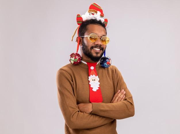 Glücklicher afroamerikanermann in braunem pullover und weihnachtsmannrand auf kopf mit lustiger roter krawatte, die weihnachtskugeln hält kamera mit lächeln auf gesicht steht über weißem hintergrund hält