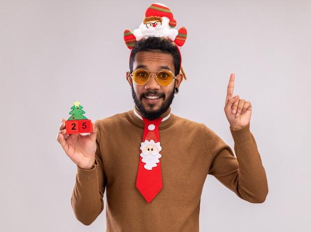 Glücklicher afroamerikanermann in braunem pullover und weihnachtsmannrand