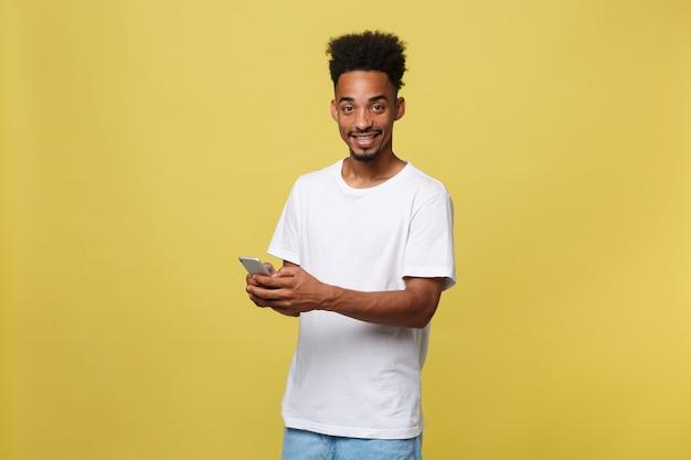 Glücklicher afroamerikanermann mit dem lächeln und handy verwendend.