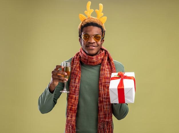 Glücklicher afroamerikanermann mit lustigem rand mit hirschhörnern und schal um hals, der glas champagner und weihnachtsgeschenk hält, das kamera betrachtet, die zuversichtlich über grünem hintergrund steht