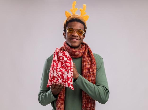 Glücklicher afroamerikanermann mit lustigem rand mit hirschhörnern und schal um hals, die rote weihnachtsmann-tasche mit geschenken betrachten, die kamera mit lächeln auf gesicht stehen über grünem hintergrund betrachten
