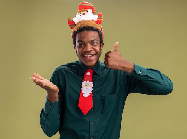 Glücklicher afroamerikanermann mit lustigem weihnachtsmannrand und roter krawatte, die kamera betrachtet, die daumen oben und unten steht über grünem hintergrund