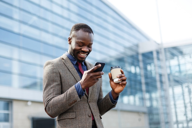 Glücklicher afroamerikanermann schaut glückliches etwas in seinem smartphone lesend