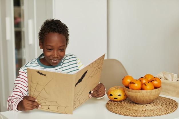 Glücklicher afroamerikanischer junge, der am tisch sitzt und interessantes halloween-geschichtenbuch liest, raum kopiert