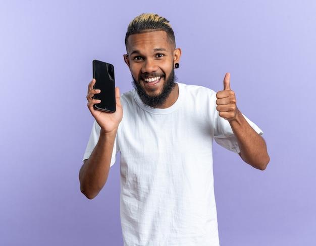 Glücklicher afroamerikanischer junger mann im weißen t-shirt, der smartphone hält und in die kamera schaut, die daumen hoch lächelnd zeigt