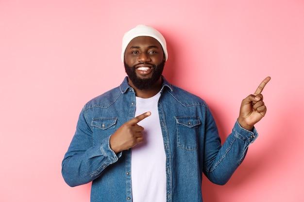 Glücklicher afroamerikanischer mann, der lächelt, mit den fingern nach rechts zeigt und promo zeigt, ankündigung macht und über rosafarbenem hintergrund steht.