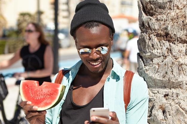 Glücklicher afroamerikanischer tourist, der frische saftige wassermelone isst und 3g oder 4g internetverbindung auf handy benutzt, während er am strand entspannt, an palme steht und nachrichten von freunden liest