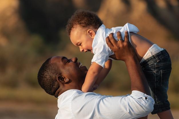 Glücklicher afroamerikanischer vater und sohn, die spaß im freien haben