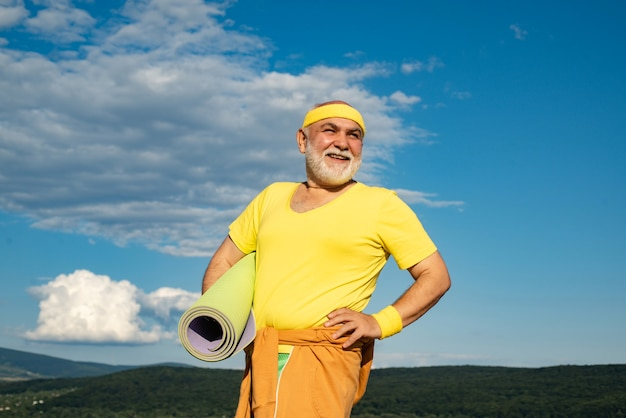 Glücklicher aktiver alter mann, der übungsmatte gesunder lebensstilkonzept sportfreiheitsruhestandskonzept hält...