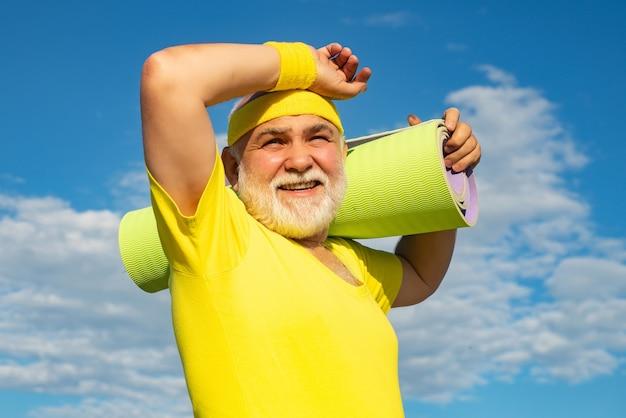 Glücklicher aktiver alter mann, der übungsmatte hält