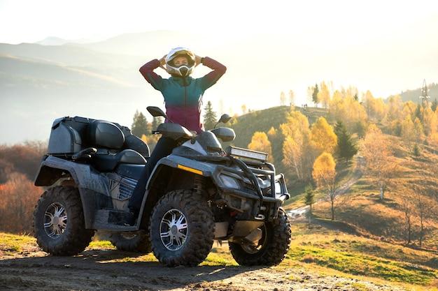 Glücklicher aktiver weiblicher fahrer im schutzhelm, der extremes fahren auf atv quad-motorrad in den herbstbergen bei sonnenuntergang genießt