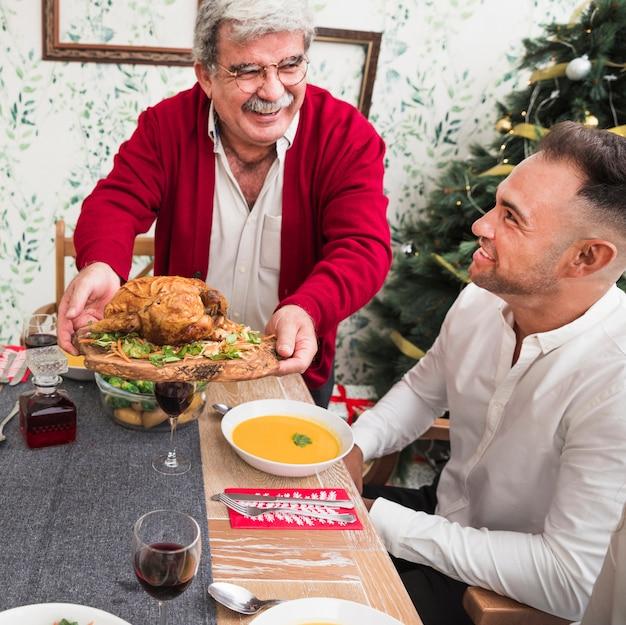 Glücklicher alter mann, der gebratenes huhn auf festliche tabelle setzt