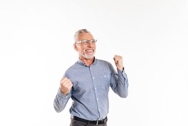 Glücklicher alter mann, der gewinnergeste lokalisiert macht