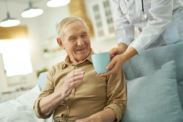 Glücklicher alter mann, der zu hause ein heißes getränk trinken wird