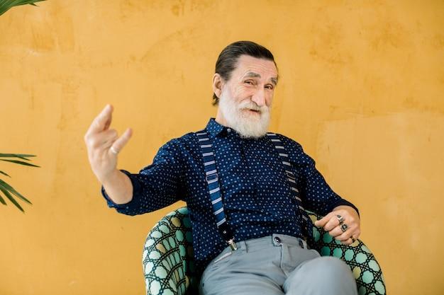 Glücklicher alter mann mit grauem bart, der stilvolle trendige hipster-kleidung trägt, im studio posiert, vor gelber wand sitzt und rock and roll zeigt