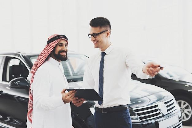 Glücklicher araber im autosalon agent holds papers.