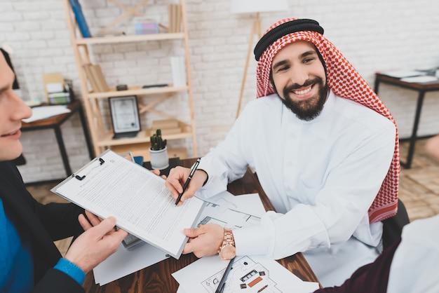 Glücklicher arabischer geschäftsmann signs financial agreement