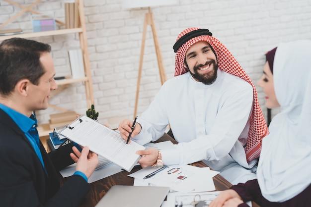 Glücklicher arabischer mann unterzeichnet vereinbarung, die zur frau lächelt.